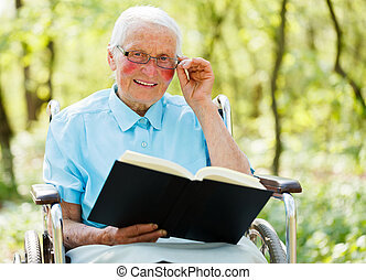 Lady in Wheelchair reading Bible - Lady with glasses sitting...