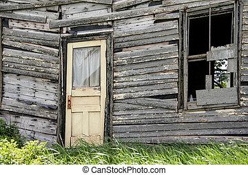 Yellow door - Sagging door on a broken down house in rural...