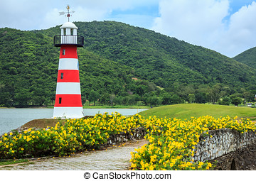 Lighthouse With Colourful Flowerbeds And Blue Sky
