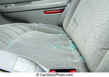 Broken glass sittin on a seat of a car