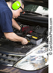 Car Mechanic - A car mechanic inspecting the car battery.