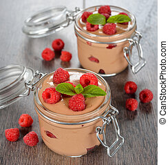 Chocolate mousse with raspberries on a brown table