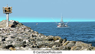 fishing boat by jetty - a large fishing boat is coming into...