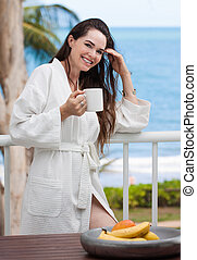 Woman holding a cup of coffee and smiling