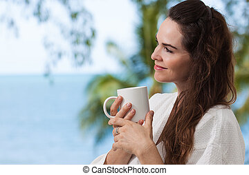 Woman enjoying morning coffee - Close-up portrait of a...