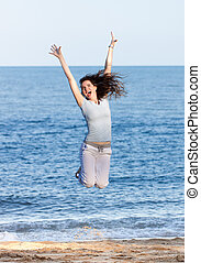 Woman jumping on a beach