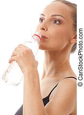 Woman in fitness wear drinking water
