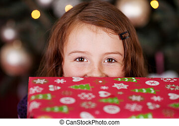 Playful little girl with a Christmas gift - Laughing eyes pf...