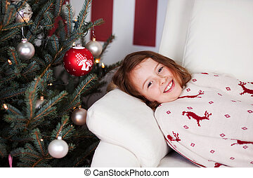 Girl lying waiting for the Christ Child - Cute smiling young...