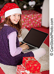 Little girl using a laptop amidst Christmas gifts - Cute...