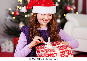 Young girl unwrapping her Christmas present - Smiling...