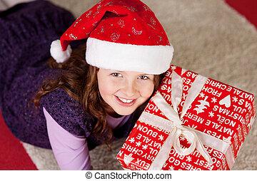 Smiling young girl with a Christmas present - High angle...