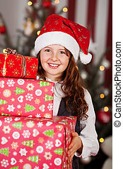 Girl carrying a pile of Christmas gifts - Cute smiling young...
