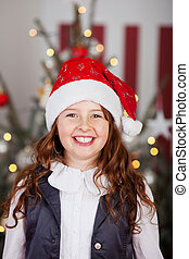 Excited young girl in a red Santa hat standing in front of a...