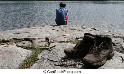 A hiker resting beside a lake - A young hiker resting beside...