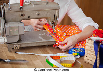 Seamstress with her sewing machine sewing a border onto a...