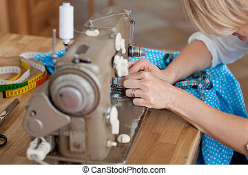 Sewing by machine - A woman sews blue fabric with machine