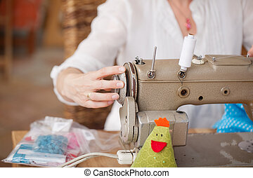 Fashion Designer Using Sewing Machine In Workshop -...