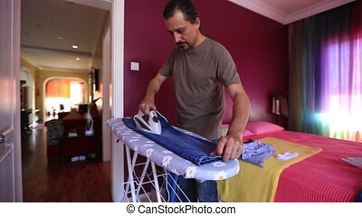 ironing - man ironing a jean at home