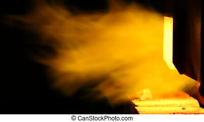 Flames from a furnace - Intense flames spuming from an open...