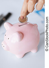 woman hand putting coin into small piggy ban - picture of...