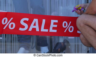 Advertising Sticker SALE - Agency worker installs a...