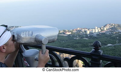 coin-operated binoculars - Tourist looking through binocular...