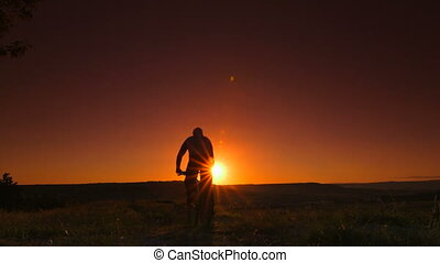 Silhouette of bicyclist against sunset. Rear view, Canon...