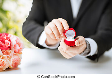 man with gift box and wedding ring - picture of man with...