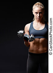 Sports woman - Athletic woman with dumbbells on a dark...