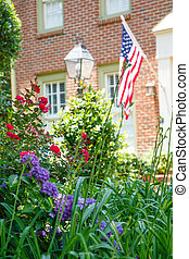 American Flag on Brick Home Behind Garden - An American flag...