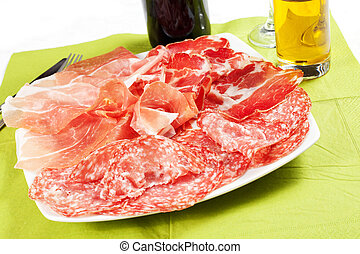 A variety of processed cold meat products on a white...