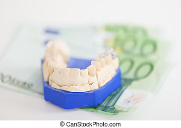 Artificial Teeth On Paper Currency In Workshop - Closeup of...