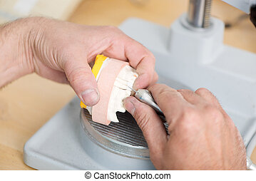 Technician's Hands Shaping Artificial Teeth With Drill -...