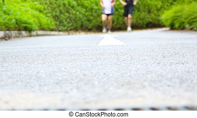 Joggers in the park running towards camera