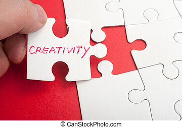 Creativity concept - Hand holding puzzle piece which written...