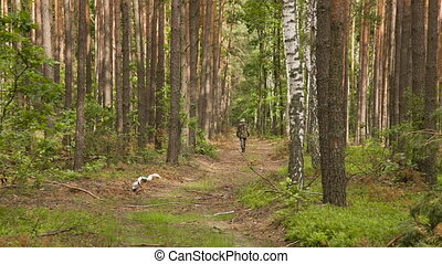 Man in camouflage walking on the footpath in summer forest