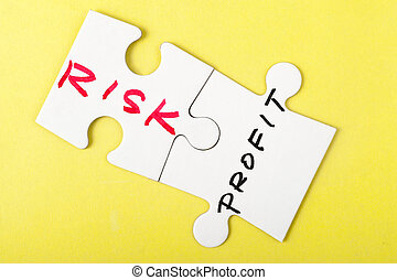 Risk and profit words written on two pieces of puzzle