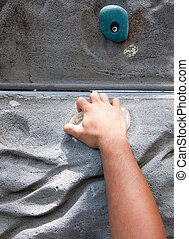 Hand hold grasping onto a wall climbing