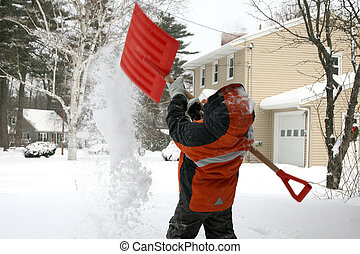 Snow Day - Five year old boy shoveling snow covered driveway...