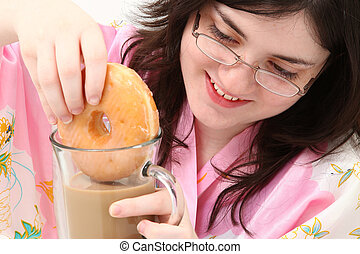 Donuts and Coffee - Adorable fifteen year old girl dunking...