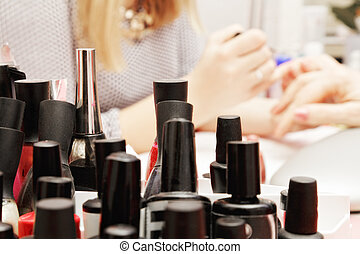 A lot of polishes with manicure procedure on background
