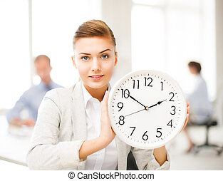 businesswoman showing white clock in office - attractive...