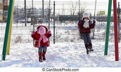 Girls in swings in winter