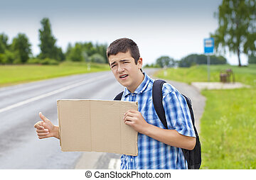 Boy hitchhiker on the road waiting for car to stop