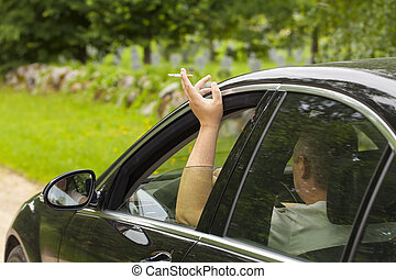 Driver with a cigarette in hand sitting in car