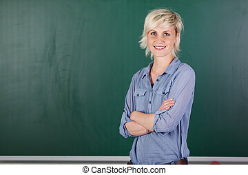 Confident Young Female Teacher In Front Of Chalkboard -...