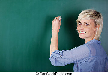 Blond Woman Writing On Chalkboard