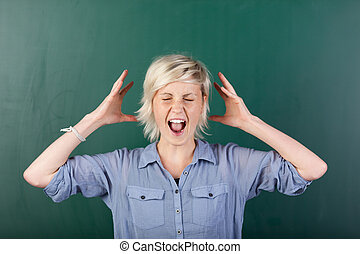 Blonde Woman Shouting By Chalkboard - Young blonde woman...