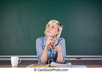 Young woman sitting in front of the blackboard and thinking...